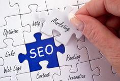 Search Engine Optimization. Jigsaw with white pieces with text connected to search engine optimization and SEO shown in upper case letters on a blue piece Stock Photography