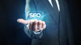 Search Engine Optimization. Businessman hand holding a virutal SEO (Search Engine Optimization) sign royalty free stock photo