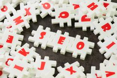 Search Engine Optimization, SEO concept, white puzzle jigsaw with alphabet building the word SEO at the center of dark chalkboard stock photo