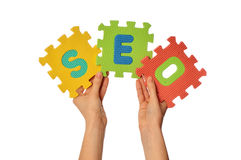 Search engine optization. Teacher holding in the hand the amusing colored puzzles with word SEO Royalty Free Stock Images