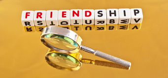 Search for friendship. Text ' friendship ' inscribed in  uppercase letters on small white cubes with hand magnifier symbolizing search, gold background Stock Photos