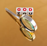 The search for God. Text ' God ' in red uppercase letters on small white cubes placed on a gold surface with a handheld magnifier symbol of searching Stock Photography