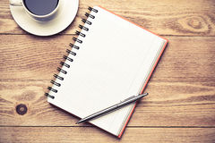 In search of inspiration. White blank notepad with cup of coffee on wooden table Stock Image
