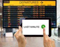 Search for last minute deals. Man search for last minute deals at an airport with your tablet Royalty Free Stock Photography