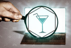 Search for leisure, clubs, parties, entertainment. Hand holds the magnifying glass in front of an open notebook. Among the many icons, attention is focused on Stock Image