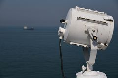 Search light and a ship in the distance stock photos