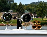 Search lights and horns. Two large searchlights and brass air horns on top of the wheelhouse of a sternwheeler boat docked on the Ohio river Royalty Free Stock Photos