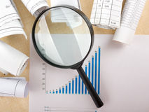Search with magnifying glass, looking for information in books, blueprints, magazines. Audit inspection. Copy space text Stock Photography