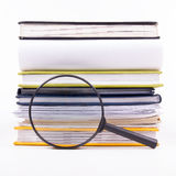 Search with magnifying glass, looking for information in books, blueprints, magazines. Audit inspection. Copy space text Stock Image