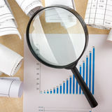 Search with magnifying glass, looking for information in books, blueprints, magazines. Audit inspection. Copy space text Royalty Free Stock Photography