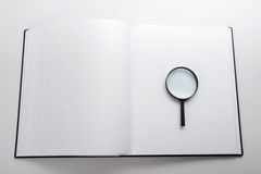 Search with magnifying glass, looking for information in books, blueprints, magazines. Audit inspection. Copy space text Royalty Free Stock Photo