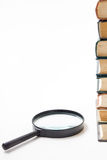 Search with magnifying glass, looking for information in books, blueprints, magazines. Audit inspection. Copy space text Royalty Free Stock Photos