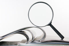 Search with magnifying glass, looking for information in books, blueprints, magazines. Audit inspection. Copy space text Royalty Free Stock Images
