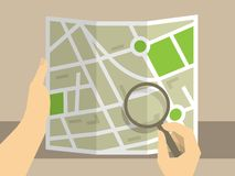 Search on map. Human hands holding map for consideration use magnifying glass Stock Image