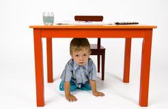 Search me. A child hides under the table Royalty Free Stock Photography