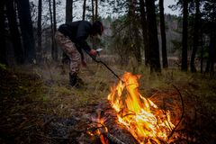 Search with a metal detector in nature. On the background of a fire royalty free stock image
