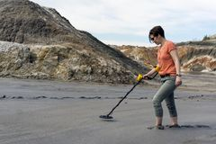 Search with a metal detector in sedimentary sediments. Woman in a deserted canyon ankle-deep in the mud searches with a metal detector stock images