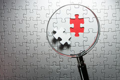 Search for missing pieces with a magnifying glass. Royalty Free Stock Photos