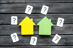 Search for a new house concept with house figure and question mark on wooden office desk background top view stock photo