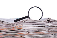 Search for news. Magnify glass over a stack of newspaper to find fresh information (isolated on white Royalty Free Stock Images
