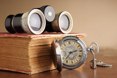 Search the past for the future. Old pocket watch with old book and old binocular Stock Photo