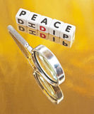 Search for peace. Text ' peace ' in uppercase black letters inscribed on small white cubes with hand magnifier symbolizing the search, gold background Stock Photo