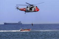 Search and Rescue Helicopter. A Royal Navy Sea King Search and Rescue helicopter lifting a casualty from a small boat in a busy shipping lane off the northeast royalty free stock photos