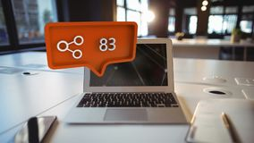 Search symbol and increasing numbers over laptop, smartphone and notebook on table. Animation of an orange speech bubble with a share symbol and increasing stock footage