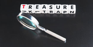 Search for treasure. Text ' treasure ' in uppercase letters on small white cubes  with hand magnifier , dark background Royalty Free Stock Image