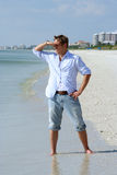 Searching. Man looking out to sea shielding eyes Stock Photography