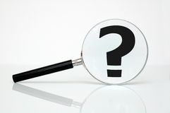 Searching. Magnifying glass and question mark - conceptual photo Royalty Free Stock Image
