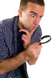 Searching. A young man with a magnifying glass searching for something Stock Image