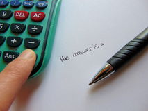 Searching for answers with calculator and pen Royalty Free Stock Images