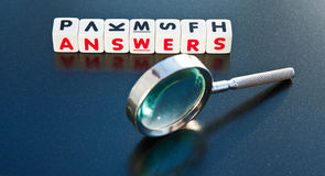 Searching for answers. Text ' answers ' in uppercase red letters on small white cubes  with hand magnifier on dark background Stock Photography