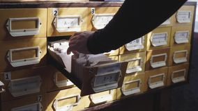 Searching in archives. Student hands searching from a filling cabinet. Searching in archives. Student hands searching from a filling cabinet stock video footage