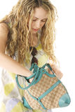 Searching in bag. Pretty curly woman searching in bag photo over white background Royalty Free Stock Photo