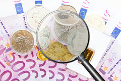 Searching the best investment. 500 euro  bank notes with gold, silver and magnifier Stock Photos