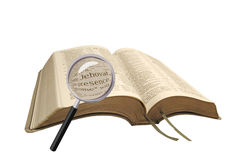 Searching the bible. Photo of open bible under scrutiny with magnifying glass searching for clues and answers royalty free stock image