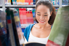 Searching for book. College stuent searching for a book in library royalty free stock photography