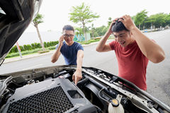 Searching Cause of Car Breakdown. Confused Vietnamese driver looking under car hood while his friend trying to find possible cause of breakdown Stock Photography
