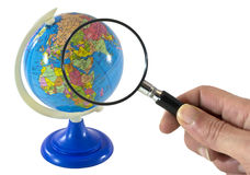 Searching concept. Hand with magnifying glass searching on globe stock photos