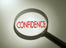 Searching confidence. Magnifying glass with the word confidence. Searching confidence Stock Images