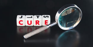 Searching for a cure. Text ' cure ' in uppercase red letters on small white cubes with hand magnifier dark background stock photography
