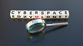 Searching in Cyberspace. Text ' cyberspace ' in black uppercase letters on white cubes with hand held magnifier , dark background Stock Image