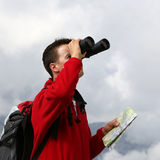 Searching the destination with binoculars in the mountains Stock Photo