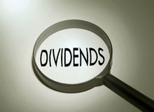 Searching dividends. Magnifying glass with the word dividends. Searching dividends stock images