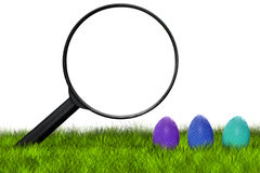 Searching Easter eggs. Loupe searching Easter eggs on grass on white background - Easter hunt Stock Photo