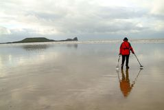 Searching at the ebb. A man with direction-finder on beach walking Royalty Free Stock Photography