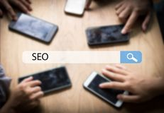Searching Engine Optimizing SEO Browsing Concept, team of busine. Ssman pressing and using phone for looking information on table Stock Image