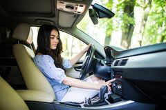Searching for favorite music. Young attractive woman smiling and pushing buttons while driving car stock images